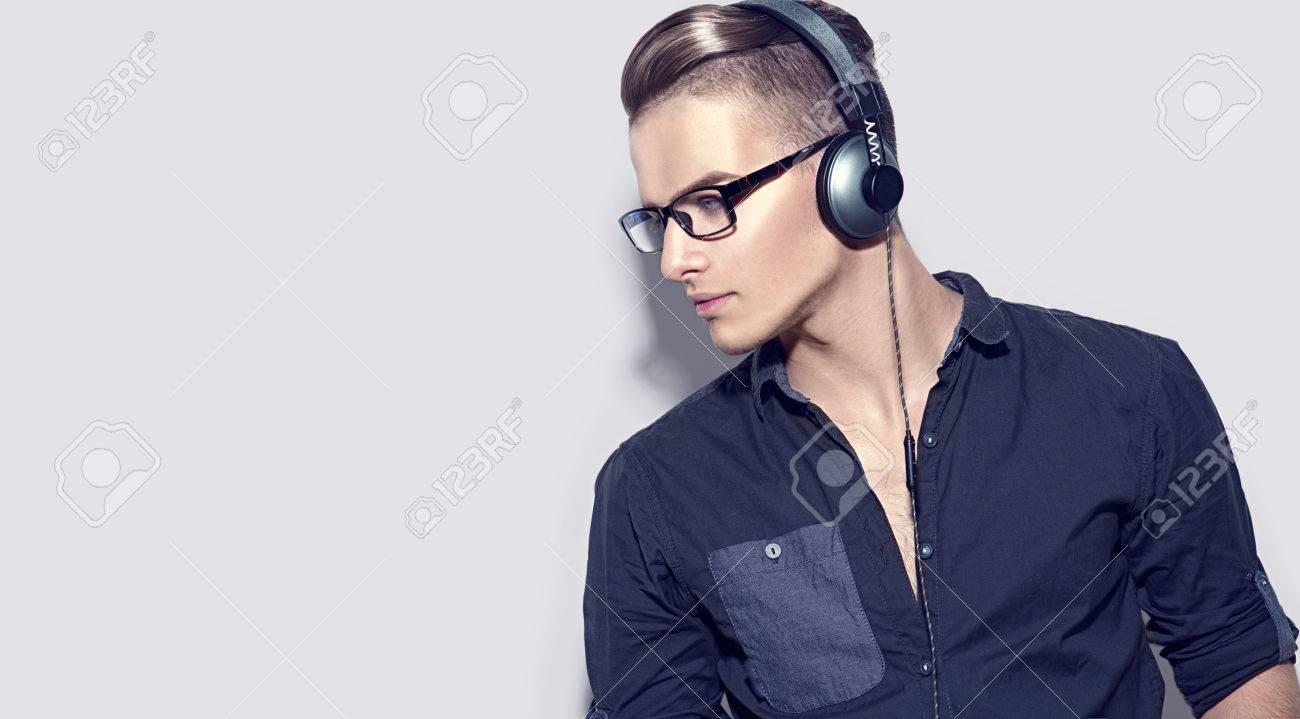 75162889-handsome-young-man-enjoying-music-on-headphones-model-guy-in-black-shirt.jpg